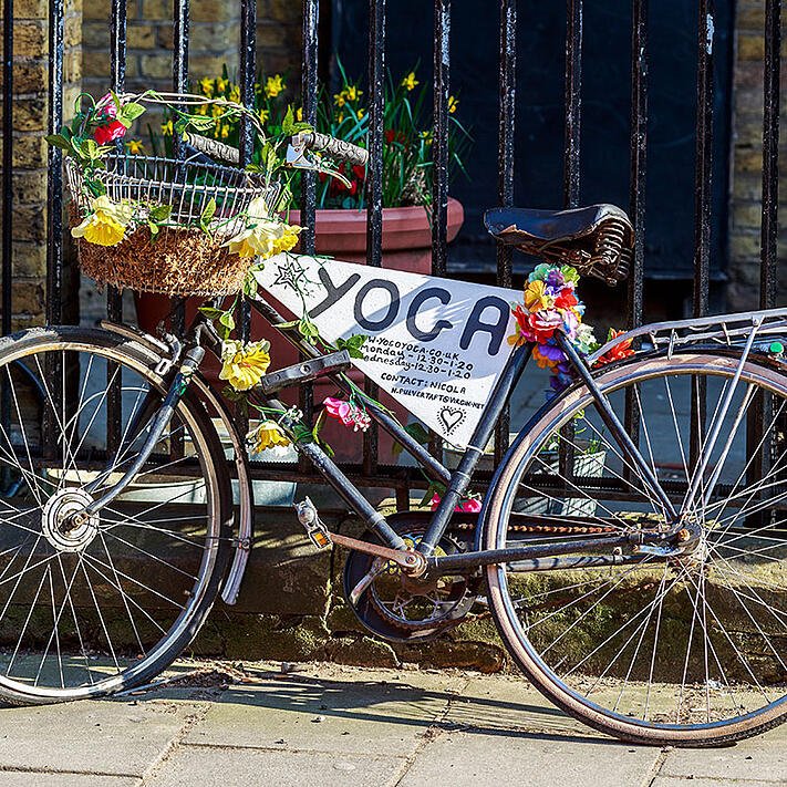 Bike with yoga sign and flowers leant against a fence
