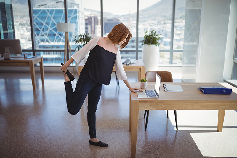 woman leaning over computer while stretching